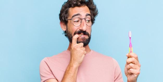 Giovane uomo barbuto con sguardo sorpreso, nervoso, preoccupato o spaventato, guardando di lato verso lo spazio della copia