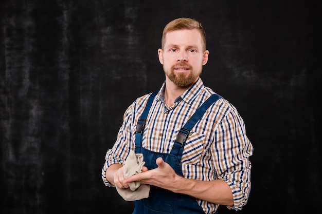 Giovane barbuto meccanico o tecnico in abiti da lavoro che puliscono le mani dopo il lavoro davanti alla telecamera in isolamento