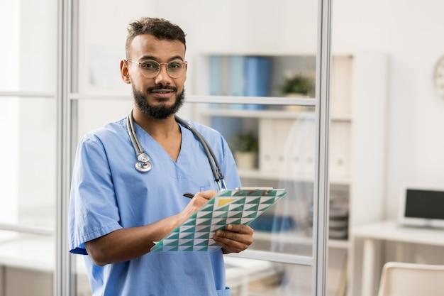 Giovane uomo di razza mista barbuto in occhiali e uniforme blu che fa le note mediche nel documento