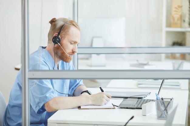 Giovane barbuto operatore in cuffia seduto al tavolo e prendere appunti nel blocco note mentre parla al telefono