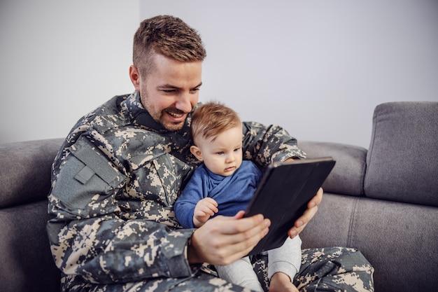 Giovane soldato barbuto seduto sul divano nel soggiorno con il suo amato figlio e stanno guardando i cartoni animati su tablet.