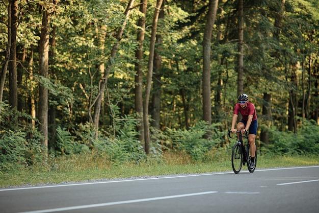 Giovane sportivo con la barba in activewear e casco protettivo in sella a bici nera tra la foresta verde estiva