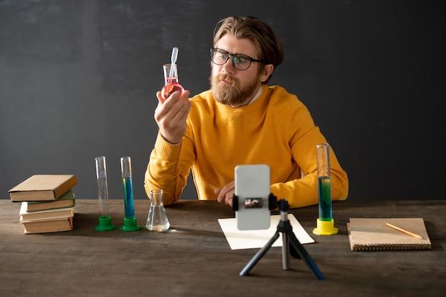 Giovane barbuto insegnante di chimica guardando il tubo con sostanza liquida rosa durante la lezione online davanti alla fotocamera dello smartphone