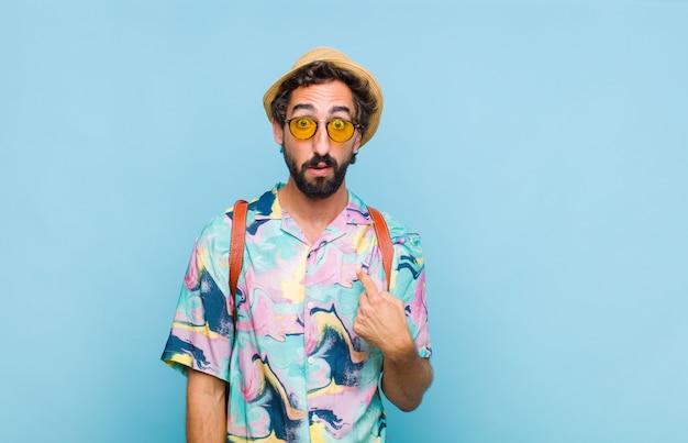 Giovane turista barbuto che si sente confuso, perplesso e insicuro, indicando se stesso e chiedendosi chi, io?