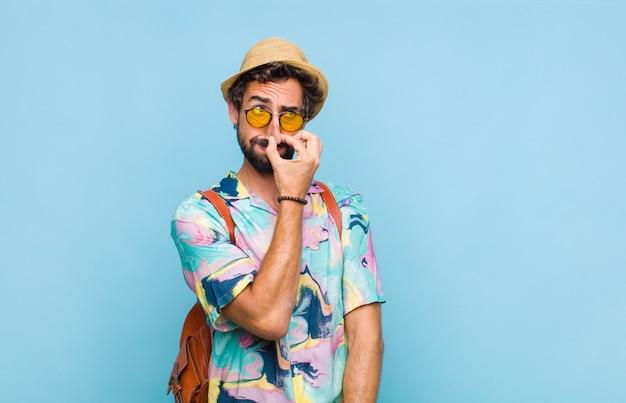 Giovane turista barbuto che si sente disgustato, tenendo il naso per evitare di annusare un fetore sgradevole e sgradevole