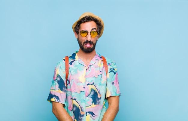 Giovane turista barbuto che si sente disgustato e irritato, sporge la lingua, non gli piace qualcosa di brutto e schifoso