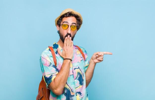 Giovane turista barbuto che si sente felice, scioccato e sorpreso, coprendo la bocca con la mano e indicando lo spazio laterale della copia