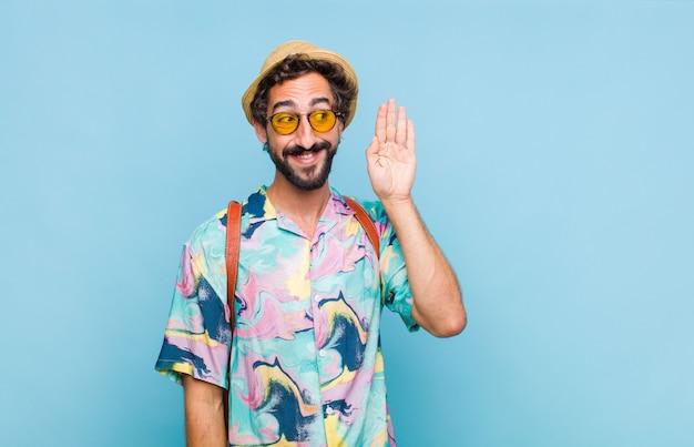 Giovane turista barbuto sorridente, guardando curiosamente di lato, cercando di ascoltare i pettegolezzi o di sentire un segreto
