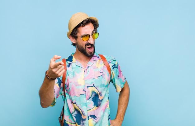 Giovane turista barbuto con un'espressione aggressiva arrabbiata che sembra un capo furioso e pazzo