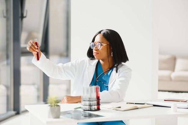 Giovane bella dottoressa afroamericana in camice bianco con uno stetoscopio. seduto a un tavolo con boccette di reagente su sfondo bianco. assistente di laboratorio femminile che studia il campione di sangue per l'analisi