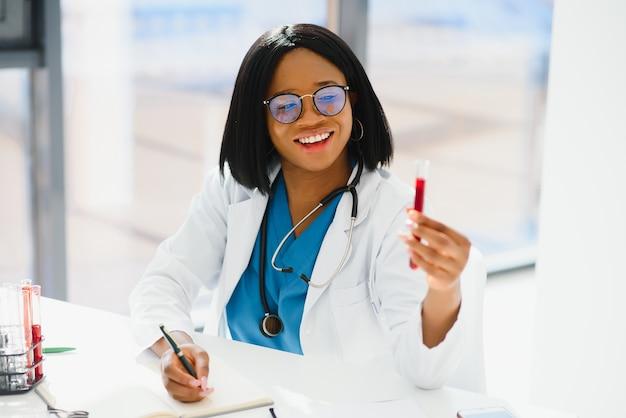 Giovane bella dottoressa afroamericana in camice bianco con uno stetoscopio.