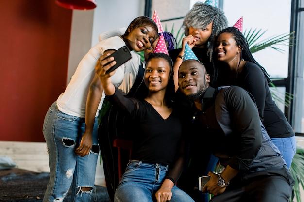 Le giovani belle ragazze afroamericane festeggiano il compleanno e fanno un selfii sul loro smartphone.