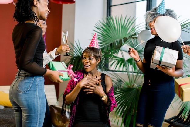 Giovani belle ragazze afroamericane con palloncini e cappelli festeggiano il compleanno e danno regali di compleanno.