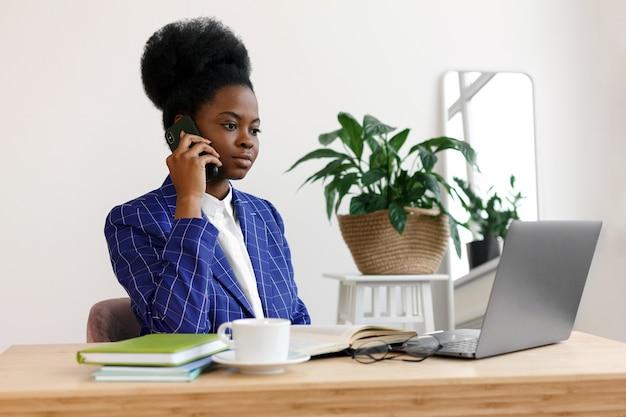 La giovane e bella donna afroamericana si siede a un tavolo guarda un computer e prende appunti