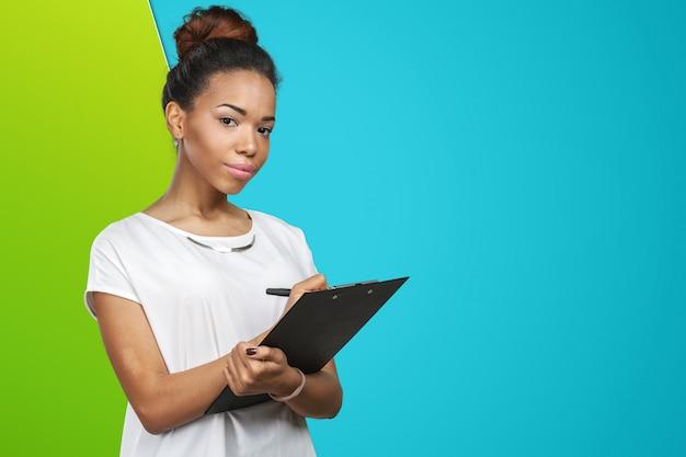 Giovane bella donna afroamericana con la lavagna per appunti