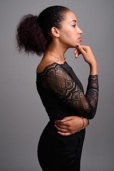 Giovane bella donna africana su grigio