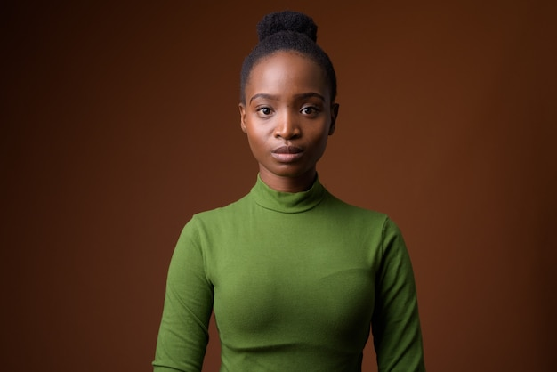 Giovane bella donna d'affari africana zulu contro backgro marrone