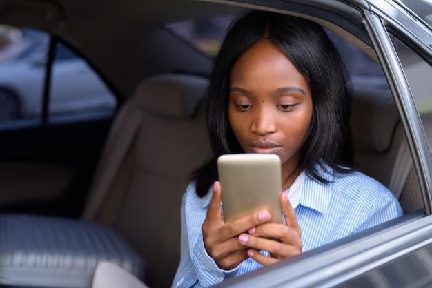 Giovane bella imprenditrice zulù africana in sella all'interno dell'auto