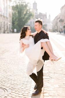 La giovane bella sposa e lo sposo asiatici sulle nozze camminano per le vie della vecchia città europea.