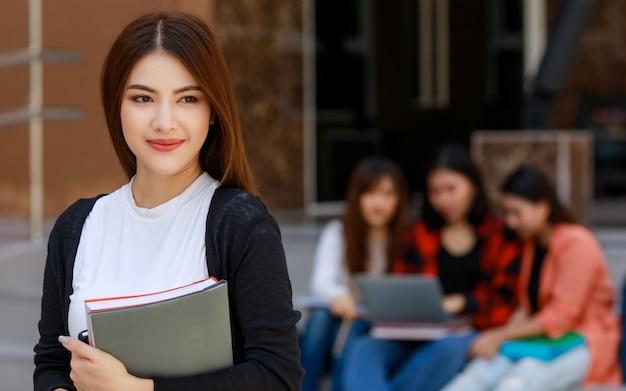 Giovani e belle ragazze studentesse di college asiatiche che tengono libri, posano davanti alla telecamera con un gruppo di amici sfocano sullo sfondo contro l'edificio scolastico. apprendimento e amicizia del concetto di amico intimo degli adolescenti.