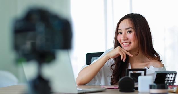 Giovane e bella ragazza asiatica che parla con la telecamera con il viso sorridente e felice durante la registrazione video trasmessa sui contenuti e la revisione dei cosmetici. vendita online e concetto di marketing.