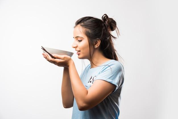 Giovane bella ragazza indiana asiatica che mangia noodle istantaneo usando le bacchette. in piedi isolato su sfondo bianco. messa a fuoco selettiva