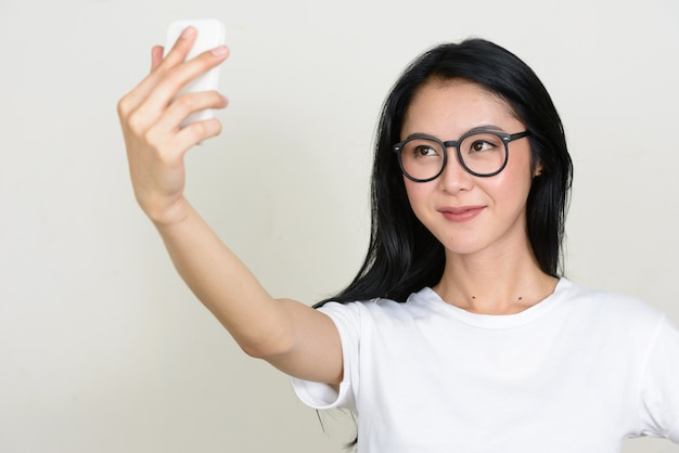 Giovane bella donna asiatica nerd indossando occhiali isolati