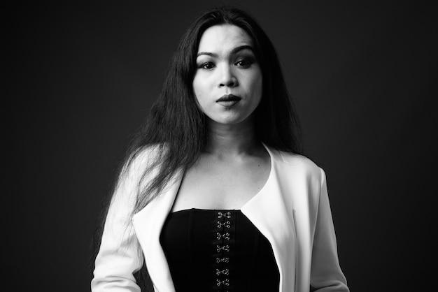 Giovane bella donna d'affari asiatica transgender in bianco e nero