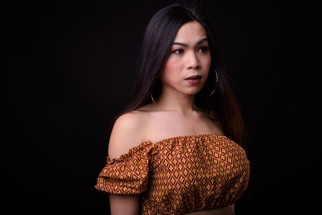 Giovane bella donna transgender asiatica contro il nero