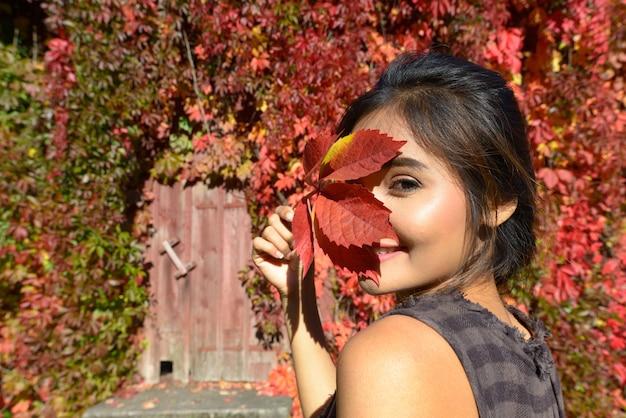 Giovane bella donna asiatica contro la casa suburbana coperta di foglie d'autunno