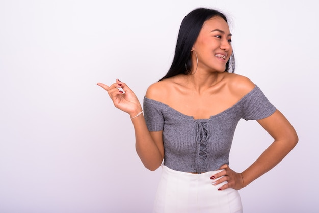 Giovane bella donna asiatica contro il muro bianco