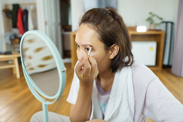 La giovane bella donna asiatica che applica compone davanti uno specchio a casa. cosmetici per pittura
