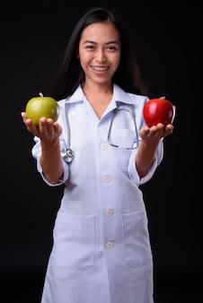 Giovane bella donna asiatica medico contro il muro nero