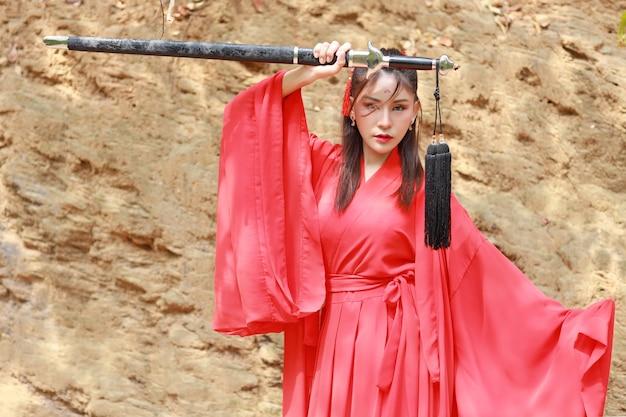 La giovane bella donna asiatica si veste nello stile del guerriero vecchio modo cinese tradizionale con la parola antica