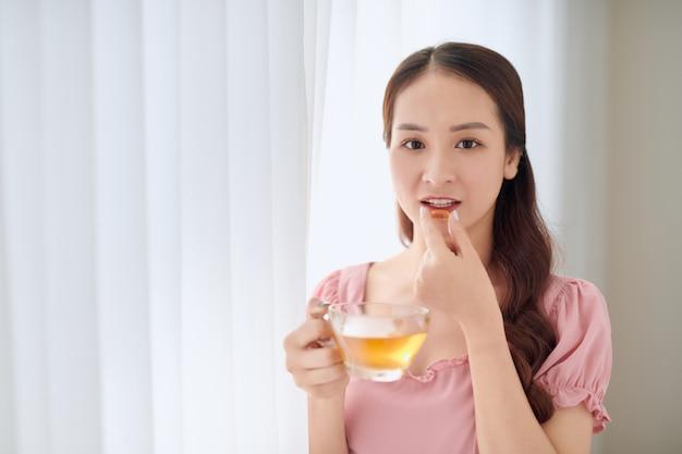 Giovane bella donna asiatica che mangia pillola e beve acqua