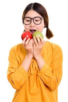 Giovane bella donna asiatica che mangia mela rossa e mela verde