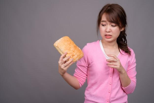 Giovane bella donna asiatica che tiene pezzo di pane