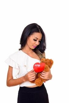 Giovane bella donna asiatica azienda orsacchiotto con cuore e amore segno isolato su bianco