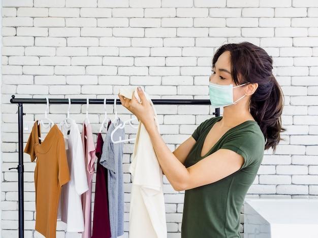 Giovane bella donna asiatica, casalinga che indossa un panno casual e una maschera protettiva che tiene la camicia, controllando la macchia sporca su di essa dopo il lavaggio