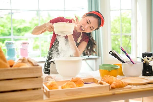 Una giovane bella donna asiatica sta cuocendo nella sua attività di cucina, panetteria e caffetteria