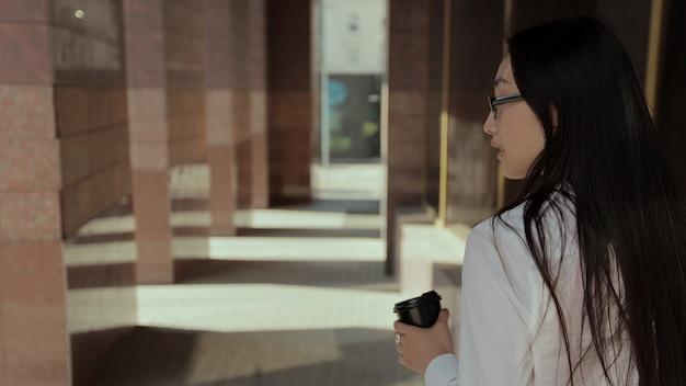 La giovane bella donna asiatica sta facendo una pausa caffè mentre si avvicina alla costruzione dell'azienda la donna d'affari in camicia bianca sta bevendo una bevanda calda hot Foto Premium