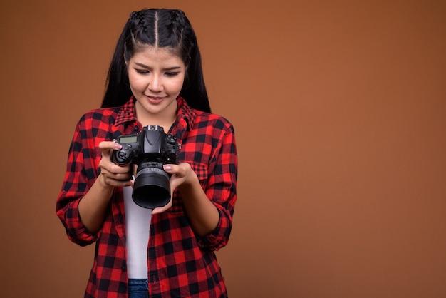 Giovane bella donna asiatica fotografo tenendo la fotocamera