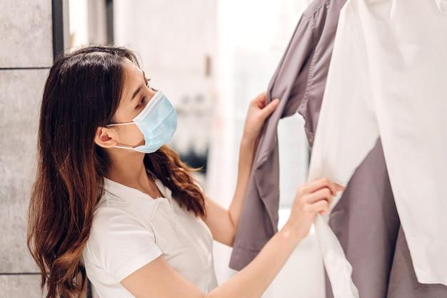 Giovane bella donna asiatica in quarantena per coronavirus che indossa una maschera chirurgica per la protezione del viso con lo shopping di allontanamento sociale e la scelta di vestiti presso store.covid19 e nuovo concetto normale