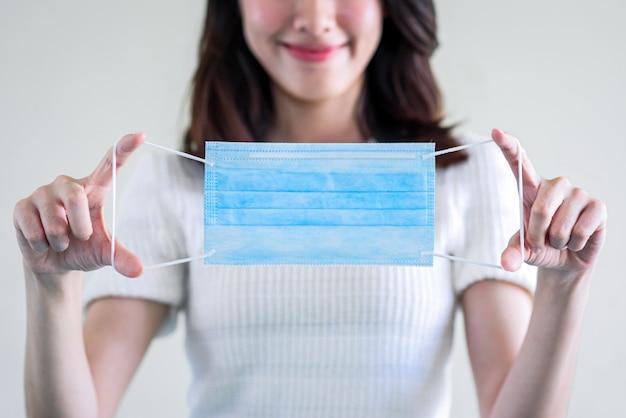 Giovane bella donna asiatica che mostra come indossare una maschera medica o che mostra come indossare correttamente la maschera chirurgica dell'igiene per gradi su fondo bianco