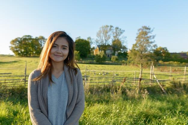Giovane bella donna asiatica in piedi nella tranquilla pianura erbosa con la natura