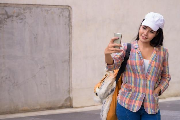 Giovane bella donna asiatica prendendo selfie utilizzando il telefono cellulare all'aperto