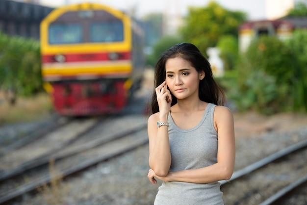 Giovane bella donna asiatica che parla al telefono alla stazione ferroviaria