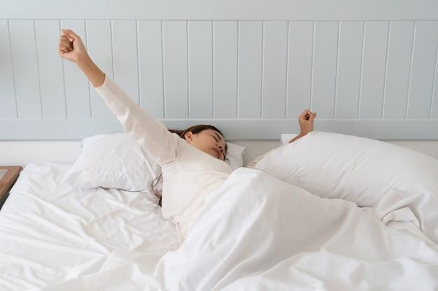 Giovane bella donna asiatica troppo pigra per alzarsi dal letto la mattina.