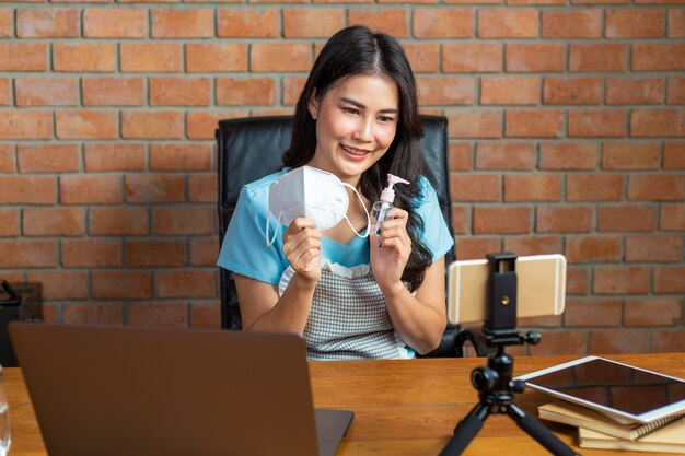 Giovane bella donna asiatica vlogger che mostra la maschera n95 e lo spray per le mani ai suoi clienti della fan page online durante il lavoro covid dal blocco domestico