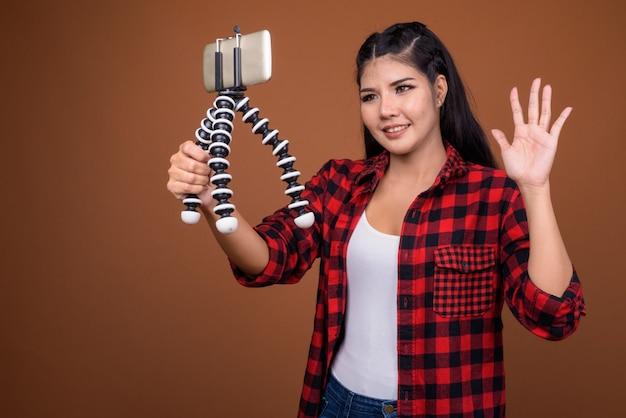 Giovane bella donna asiatica vlogging con il telefono cellulare